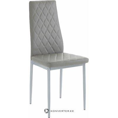 Mīksts pelēks krēsls uz metāla fasādēm